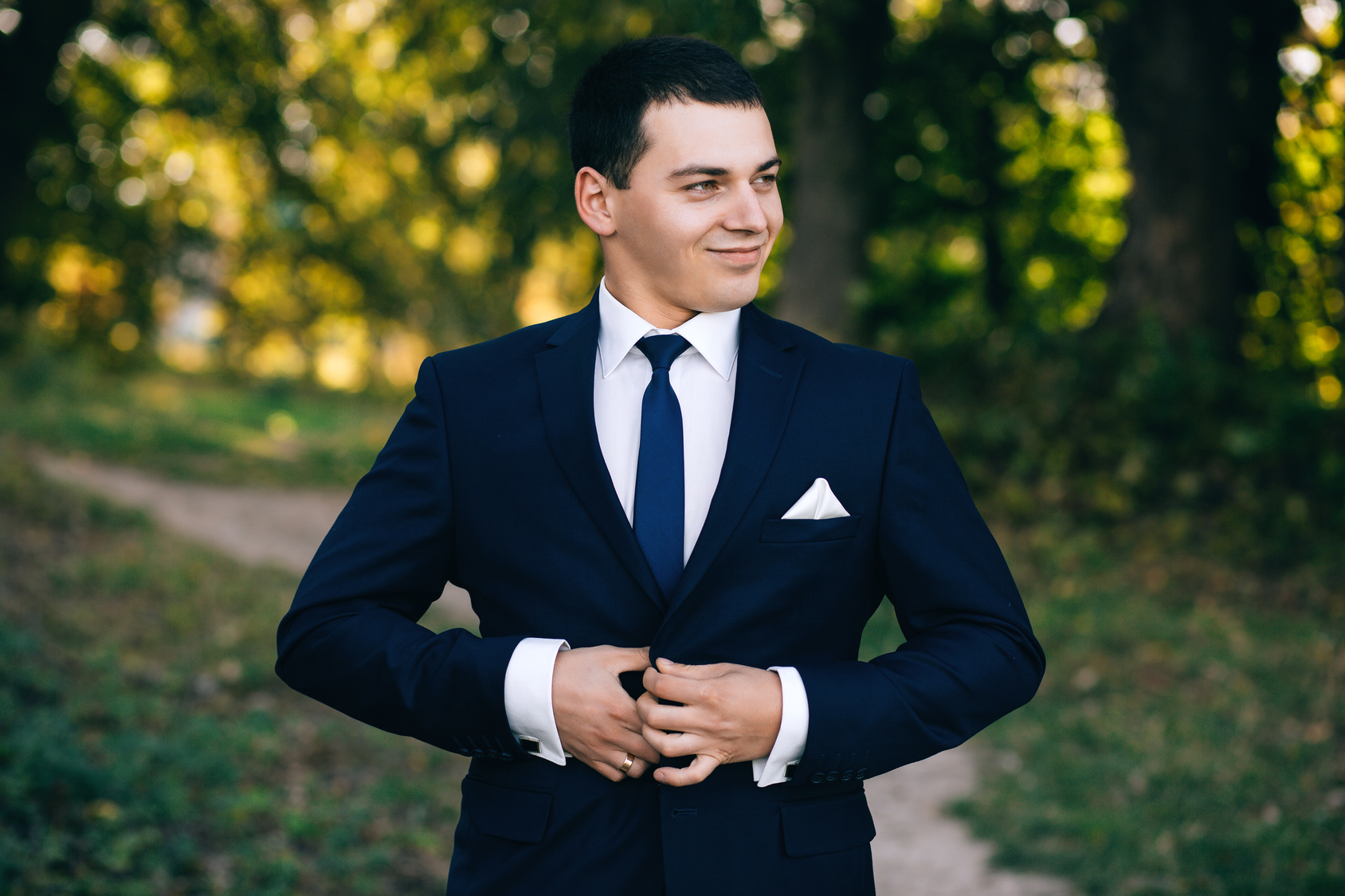 confident, cute groom man in a stylish business suit, outdoors, autumn. Portrait of the groom in the park on their wedding day. Rich groom man on their wedding day